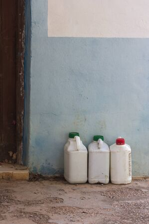 Three old insecticide containers forgotten next to a wall painted white and blue