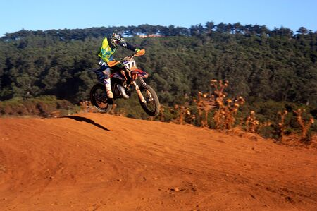 A motorcycle jumping forward on a slope of the dirt track on which it circulates Banco de Imagens