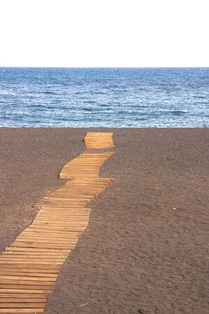 A wooden path that crosses the sand from the beach to the sea