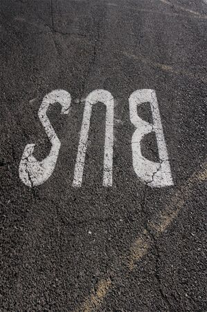 Letters painted on cracked asphalt indicating the place where the bus stop is