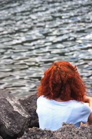 A red-haired woman looks at the waves of the sea at sunset sitting on the rocks of the shore Фото со стока