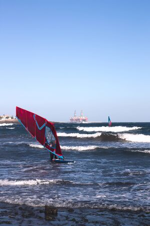 A windsurfer travels over the ocean water with a board thanks to the force of the wind