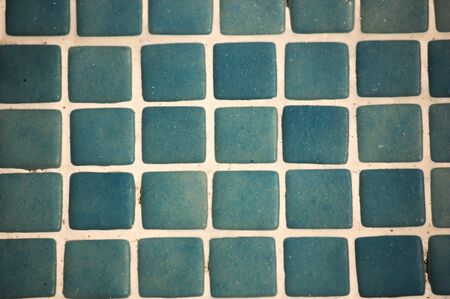 Close-up of blue and vintage-style tiles that form a grid of small white squares