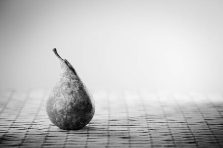 Black and white image of a pear standing on a table with a checkered mat and white background Фото со стока