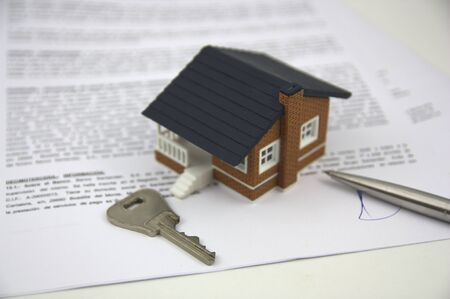 A house, a key to a door and the signature on the bank papers close the business Фото со стока