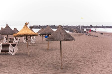 Close-up of straw umbrellas located on the beach next to the hammocks for tourists and vacationers who come to them to rest Фото со стока