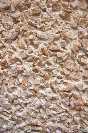Close-up of a wall with stone mono layer mortar projected on the surface