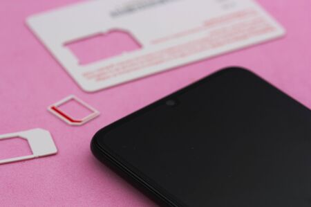 Some mobile phone cards (sim cards) next to a next-generation smart phone on a pink background.