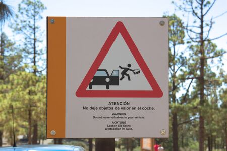 A sign in a tourist area reminds you in English, Spanish and German that you should not leave valuables in the car