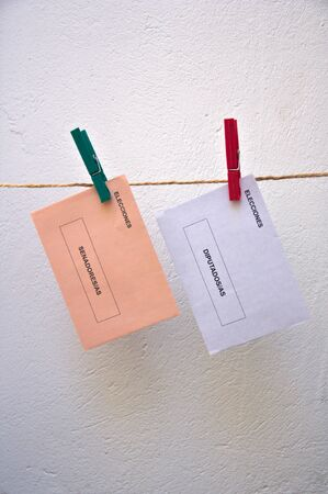 A pair of ballots for national elections in Spain hung with two clamps on a cable run