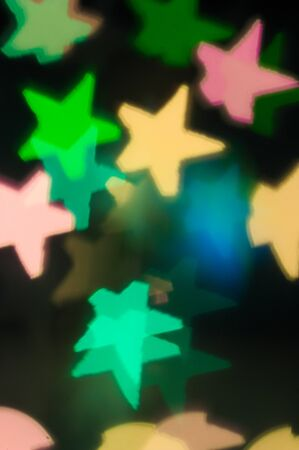 A background with colored stars for Christmas motifs, cards, congratulations on New Year and Christmas Фото со стока