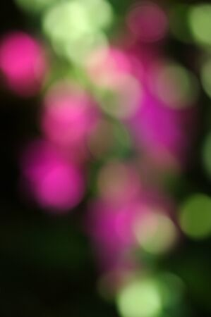Defocused image of purple and green colored lights with a dark background, perfect for times of celebration Christmas, New Year, etc.