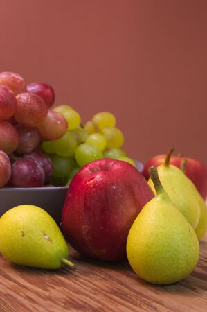 A still life with fruits such as pears, apples and grapes with a brown background and space to add texts, copy space