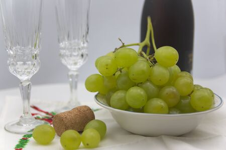 A table prepared with Christmas motives waiting for the end of the year and thus celebrate with a glass of champagne and the traditional grapes of luck the arrival of the new year Stock Photo