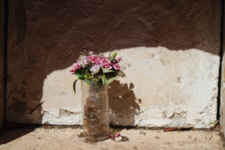 Niche with a simple bouquet of artificial flowers covered in dust in a niche without gravestone Foto de archivo