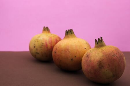 Three mollar type grenades aligned on a diagonal of the image on pink and brown background Stok Fotoğraf