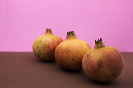 Three mollar type grenades aligned on a diagonal of the image on pink and brown background Stok Fotoğraf - 133941918