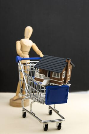 A dummy carries a shopping cart with a miniature house with a dark background. Concept of buying houses.
