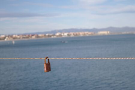A padlock tied to a railing symbolizing a secret by the seashore in a tourist area