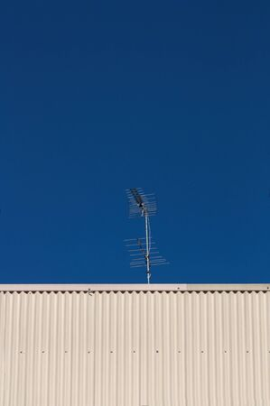 Image of a digital terrestrial television antenna with blue sky in the background and space for texts or graphics. Copy space