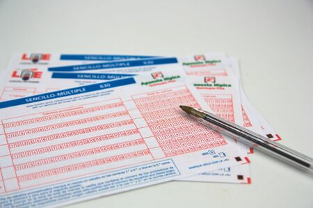 2019. España. Entradas para apuestas ecuestres de Loterías estatales en España vacías junto a un bolígrafo sobre una mesa blanca