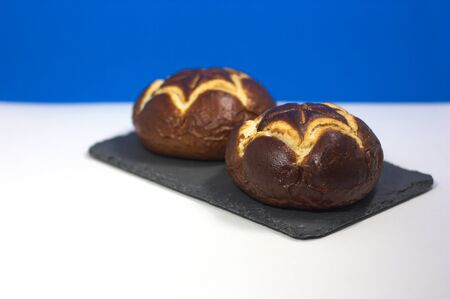 A pair of German lye rolls with the colors of the Bavarian flag in the background