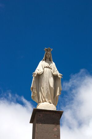 Miraculous white marble statue looking towards the ground with blue sky with some clouds in the background