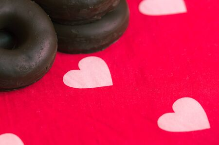 Some chocolate coated cookies on a red surface with white hearts and space for texts, copy space Banco de Imagens