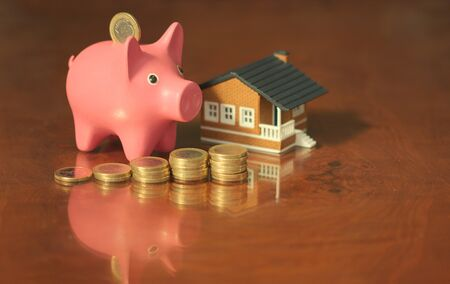 A piggy bank with a small house and some coins on a wooden table with reflections. Conceptual image about saving for the purchase of a home.