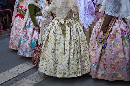 Group of women dressed in their costumes falleras regional after making the Ofrenda (floral offering) to the Virgin Mary in the Plaza de la Virgen in Valencia, Spain