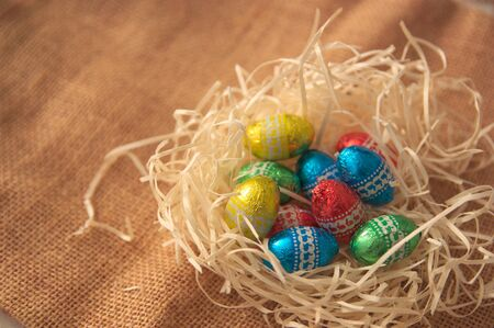 Close-up of some Easter eggs of different colors in a nest of natural straw on an also natural jute surface. In the image there is space for texts or graphics Stock fotó