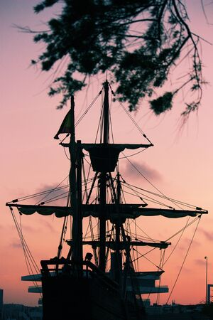 Silhouette image of a 15th century Spanish caravel boat framed by tree branches while moored in the harbor
