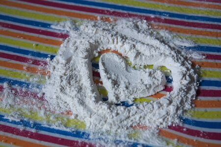 Close-up of a heart drawn on flour and which reveals a surface of striking colorful horizontal lines