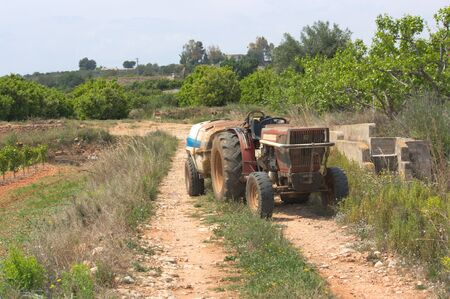 Image of a tractor dedicated to maintaining agricultural fields stands in the middle of a rural road