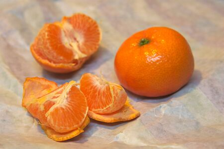 A tangerine peeled and open next to another with skin on a crumpled wrapping paper Stok Fotoğraf