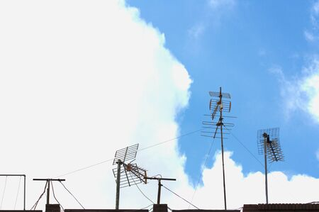 The silhouettes of antennas that tune the DTT television signal in a tall building contract with clouds and blue sky