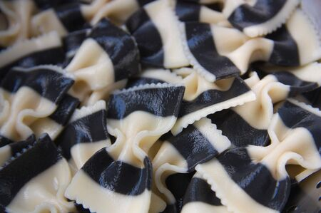 Close-up of a plate full of boiled pasta in the form of two-color ties and seafood flavor, black and white Stok Fotoğraf