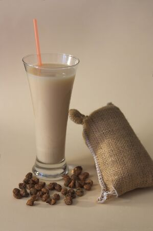 A tall glass of horchata with a few chufas and a typical bag of cream with a cream-colored bottom Stok Fotoğraf