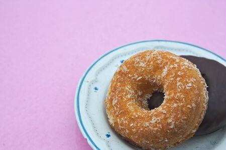Two doughnuts one with coconut and one with chocolate on top on a plate and a pink background to add texts (copy space)