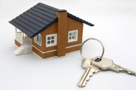 A small house and some keys on a white table symbolizing the purchase or mortgage of a house