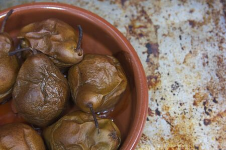Freshly baked pears in a clay pot on the textured baking sheet and with space for texts (copy space)