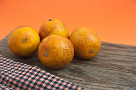 Some blood oranges on a wooden board and orange background with space for texts