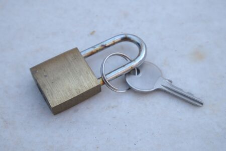 Close-up of a padlock next to the key that opens it on a weathered gray marble surface