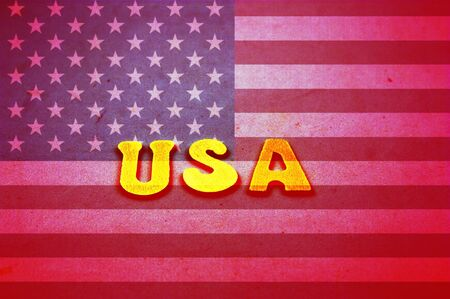 Image of the American flag on which the letters USA appear in yellow. The image has grunge textures and a reddish color
