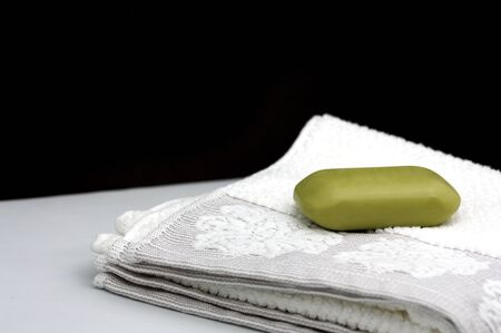 Some white towels on which there is a bar of soap, black background in which there is space for texts