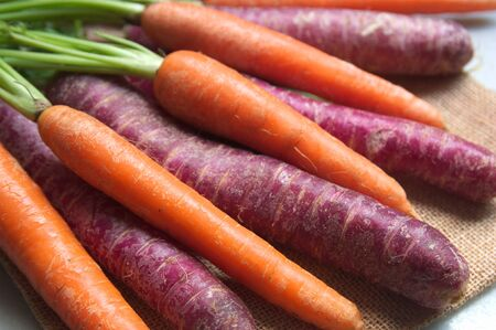 Purple and orange carrots on a brown sackcloth with natural window light