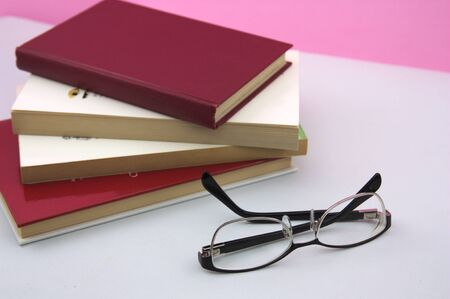 Some books stacked on a table where there are also reading glasses with space for texts and pink background