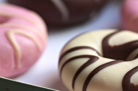Closeup of a box with some donuts of different flavors and colors such as strawberry and chocolate