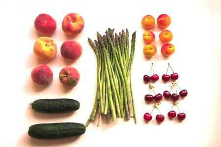 Plane from above a table where various fruits and vegetables are ordered such as asparagus, peaches, apricots, cherries, cucumbers. Flat lay