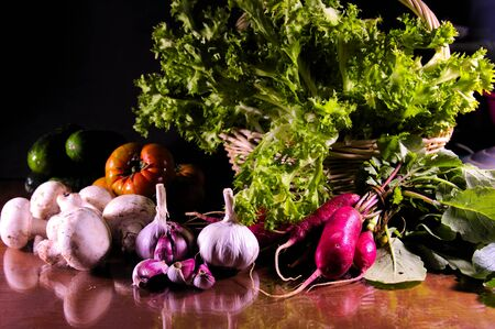 Image of a still life of vegetables with a dark background in which we see purple garlic, mushrooms, radishes, lettuces, tomatoes, cucumbers on a glass table in which the products are reflected